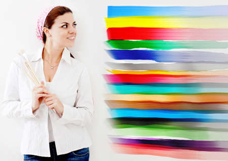 Woman painting a wall of the house and choosing from different colors  photo