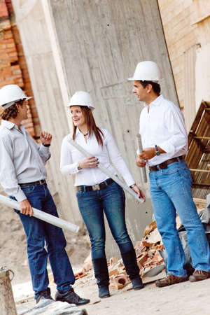 Group of architects at a construction site holding blueprints  photo