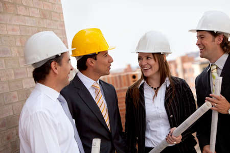 Group of engineers at a construction site talking and smiling photo
