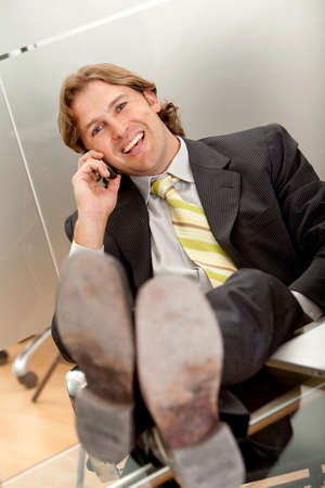 Confident business man on the phone and his feet on the desk  photo