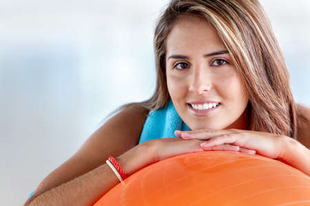 fitness ball: beautiful woman portrait at the gym smiling leaning on a pilates ball