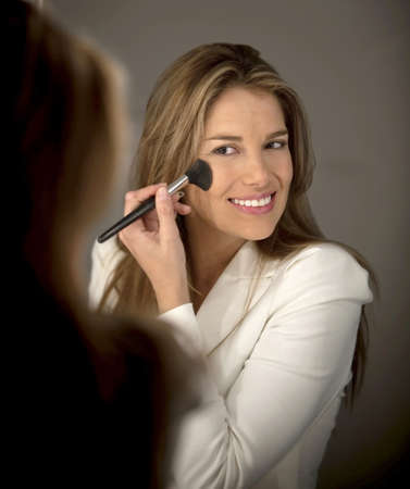 Woman putting blush on her cheeks - make up concepts photo