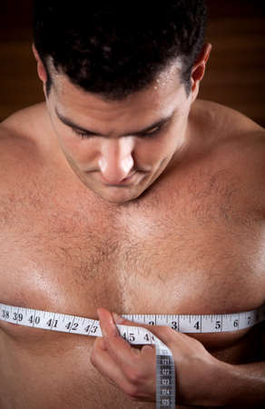 Handsome man with a muscular body measuring his chest at the gym photo