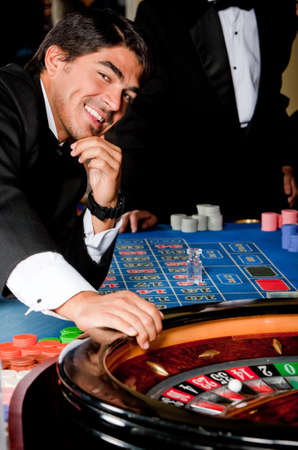Man in a casino playing on the roulette  photo