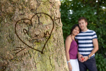 Happy couple in love with their initials carved in a tree  photo