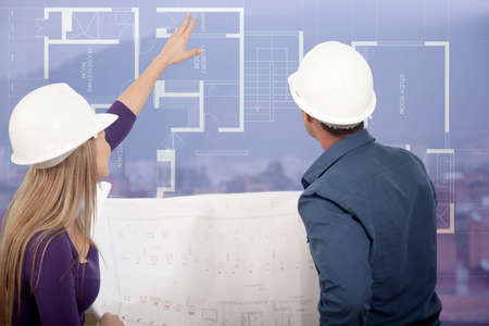 Architects at a construction site looking at the blueprints   photo