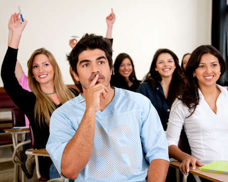 amongst: Doubtful man amongst a group of university students in a classroom rising their hands