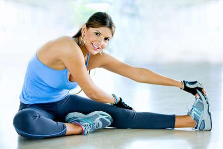 растягивание: Женщина делает упражнения на растяжку на полу в тренажерном зале