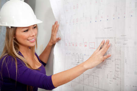 Female engineer at a construction site looking at blueprints   photo