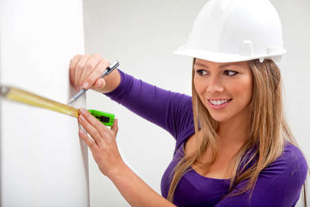 female architect: Female architect taking measurements of a wall and smiling