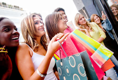 Group of shopping people holding bags looking at a window 