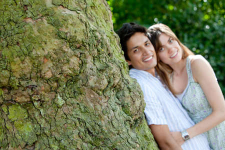Happy couple in love leaning on a tree - outdoors   photo