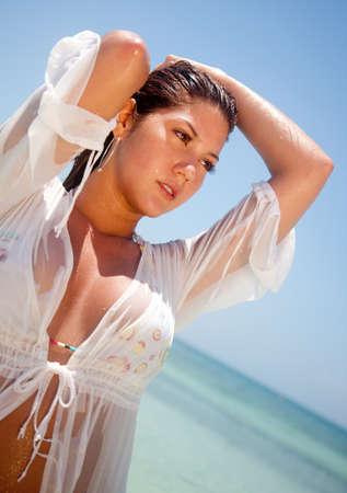 mojado: Mujer sexy en la playa con una camiseta mojada