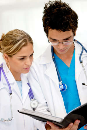 historia clinica: Un par de m�dicos en el hospital mirando a la historia cl�nica