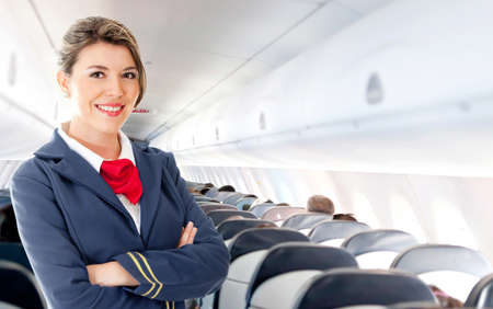 air hostess: Beautiful air hostess in an airplane smiling  Stock Photo