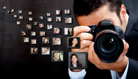 Male photographer holding the camera with pictures flying around  photo