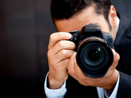 Male paparazzi holding a digital camera and shooting  photo