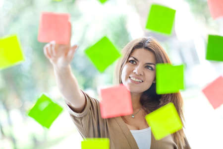 eventful: Multitask woman pointing at post-its and smiling Stock Photo