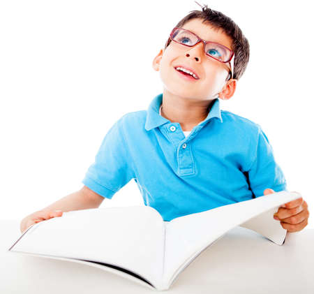 Thoughtful boy fantasizing and reading a book - isolated over white  photo