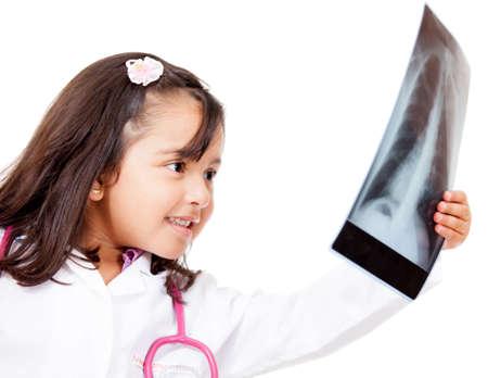 ni�as jugando: Ni�a jugando m�dico y lookig en una radiograf�a aislado m�s de blanco