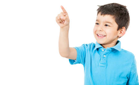 Happy boy pointing with his finger - isolated over a white background  photo