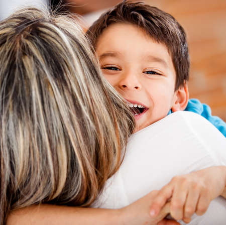 Happy boy hugging his mother and smiling  photo