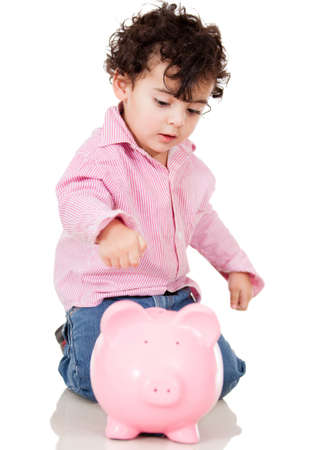 Little boy saving money in a piggybank - isolated over a white background Stock Photo - 13761846