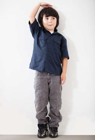 Boy checking his height against a wall - isolated over white  photo