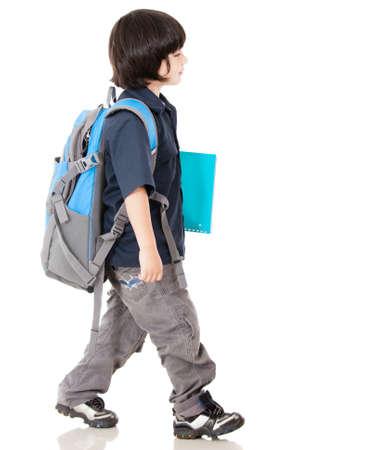 niño con mochila: Chico caminando a la escuela - aislados en un fondo blanco Foto de archivo