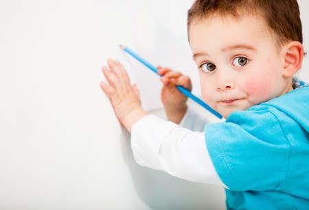 niños dibujando: Niño pequeño dibujo en una pared blanca