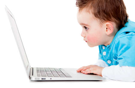 Little boy looking at a laptop computer - isolated over white  photo