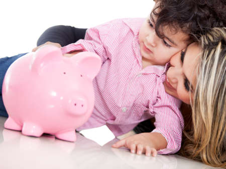 Family saving in a piggybank - isolated over white  photo