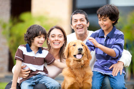 nios hispanos: Familia al aire libre con un perro mirando muy feliz