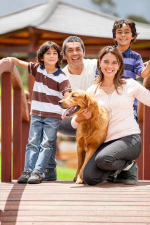family relationships: Happy family having fun outdoors with their dog  Stock Photo