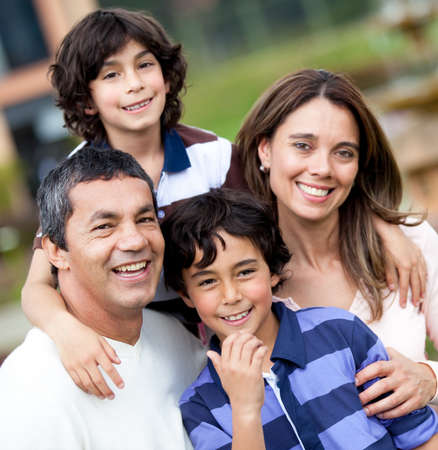 hispanic children: Portrait of a beautiful family smiling and looking happy - outdoors  Stock Photo