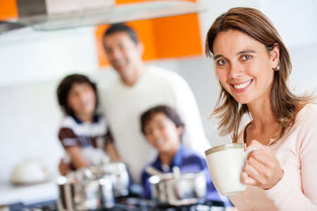 Happy mother holding a cup of coffee in the kitchen  photo