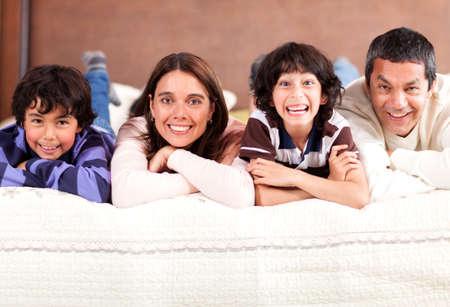Hermosa familia en la cama en su casa y sonriendo photo