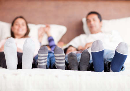 Family lying in bed together - focus on feet  photo