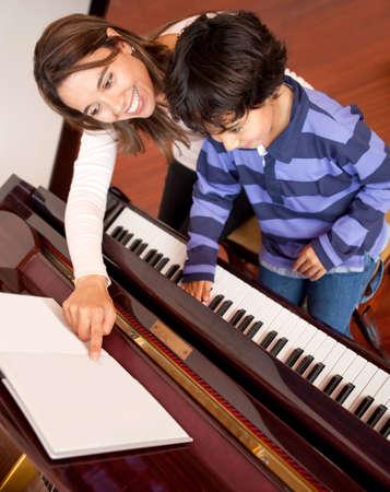 fortepian: Chłopiec bierze lekcje gry na fortepianie w domu