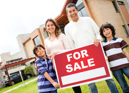 Happy family holding poster of a house for sale  photo