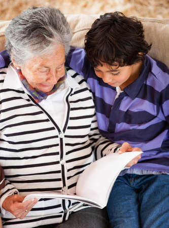 Grandmother reading a story to her grandson at home  photo