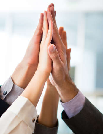 Group of people celebrating with a high-five - business teamwork  photo
