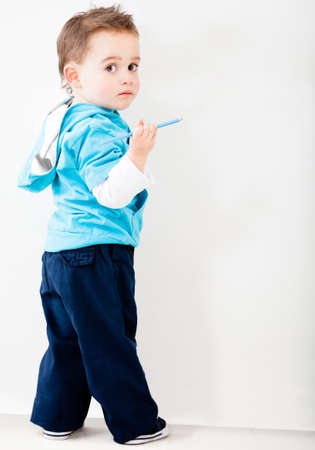 children painting: Naughty boy drawing on a  white wall  Stock Photo