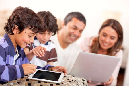 technological: Technological family with a laptop and tablet computer at home  Stock Photo
