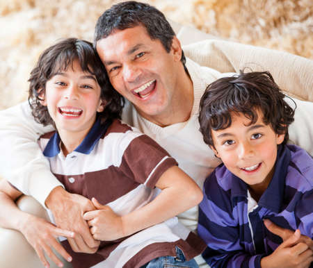 Playful father with his two sons smiling at home  photo