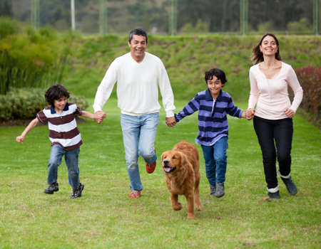 Happy family running outdoors chasing a dog photo