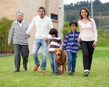 Beautiful family walking outdoors with a dog and smiling  photo