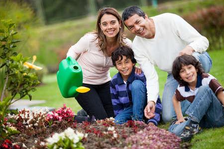 familia en jardin: Familia en el patio regando las plantas y sonriente Foto de archivo