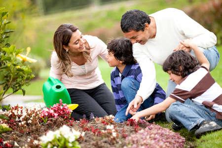 familia en jardin: Huertos familiares felices juntos y cuidar de la naturaleza Foto de archivo
