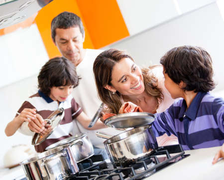 latin family: Family cooking together in the kitchen and looking happy